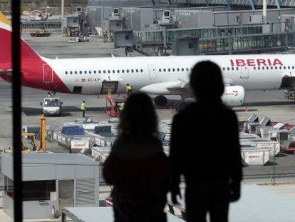 Dos personas miran un avión de Iberia desde la terminal 4 de Barajas.