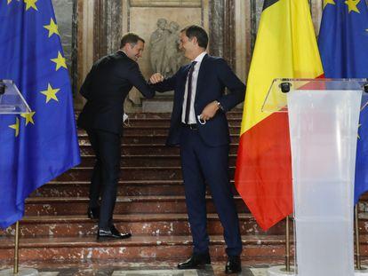 El futuro primer ministro belga, el liberal flamenco Alexander De Croo (a la derecha) saluda al socialista valón Paul Magnette, con quien ha liderado las negociaciones, durante la rueda de prensa en la que se ha anunciado la formación del gobierno belga esta mañana.