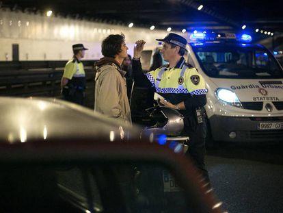 Un agente de la Guardia Urbana hace el control de alcoholemia a un conductor.