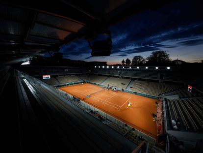 Panorámica de la pista Simonne Mathieu de Roland Garros, con luces artificiales, durante un partido al anochecer entre Khachanov y Majchrzak.