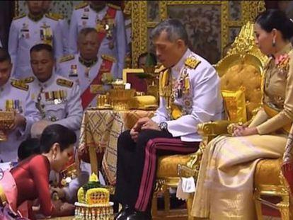 El rey Maha Vajiralongkorn de Tailandia, sentado junto a su esposa, durante la ceremonia para investir a su concubina.