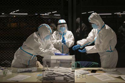 Los miembros de una mesa electoral de Barcelona se colocan los equipos de protección para recibir en la última hora para votar a las personas infectadas del virus o en cuarentena.