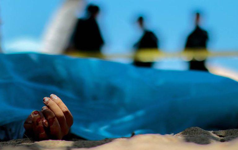 Forenses observan el cuerpo de un hombre muerto en Acapulco, en 2016.