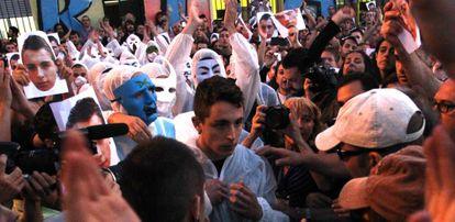 Alfonso Fernández (en el centro, con el rostro descubierto) sale de la Parroquia de San Carlos Borromeo para entregarse.