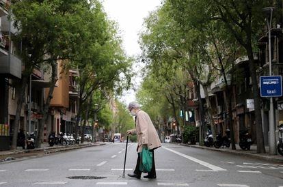 Una mujer mayor camina por las calles de Barcelona.