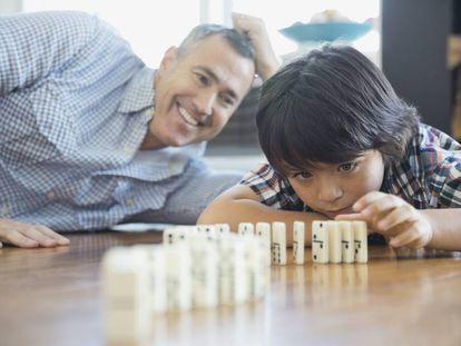 Un padre juega al dominó con su hijo.