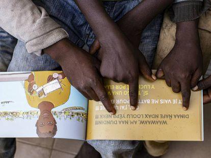 Niños acogidos en el centro La Maison de la Gare, miran el libro 'Solo la vida'.