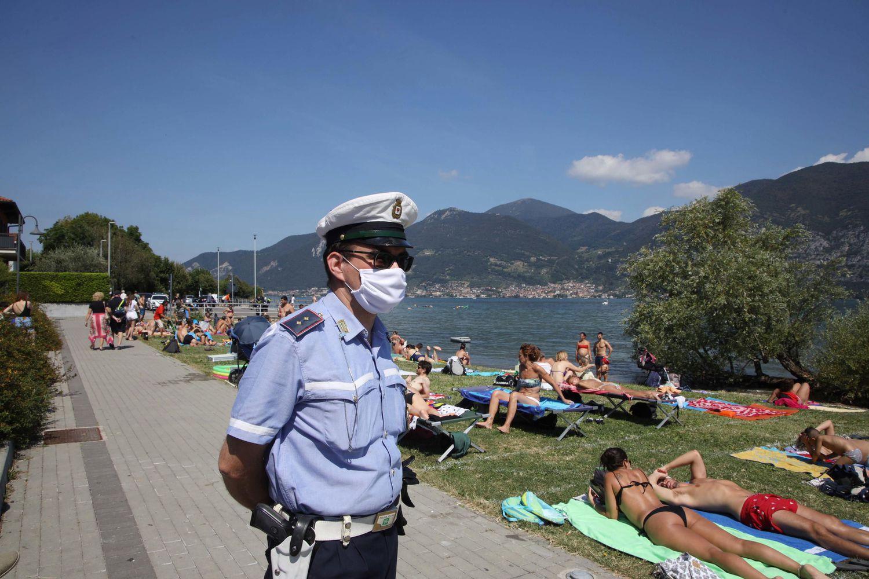 La policía local vigila en la playa del lago Iseo, en la región de Lombardía (Italia), para evitar aglomeraciones.
