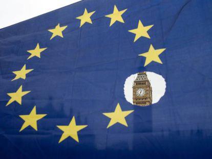 El Big Ben se observa a través de una bandera europea agujereada.