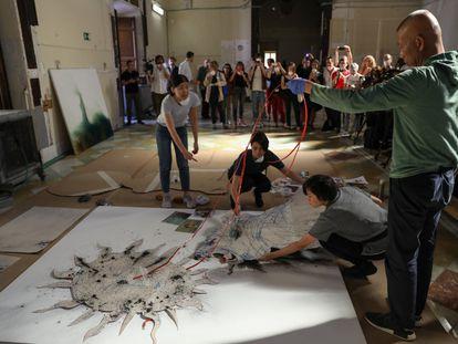 Cai Guo Qiang, en el Salón de Reinos, trabajando con su equipo en la obra 'El alquimista', basada en una antigua leyenda en la que un león se quería comer el Sol, lienzo que formará parte de la exposición, 'El espíritu de la pintura', que se inaugura el 25 de octubre en el Museo del Prado. Él controla todo el proceso, pero sus colaboradores le ayudan a situar las plantillas, los cables, la pólvora, los pesos para que todo se mantenga en su sitio durante la explosión.