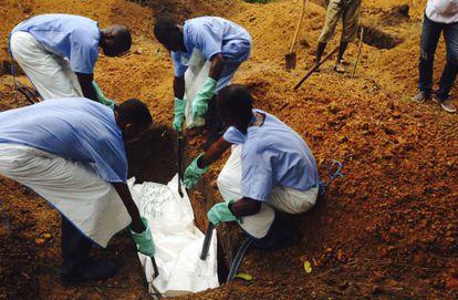Voluntarios en Sierra Leona entierran un cuerpo de forma segura para evitar el contagio.