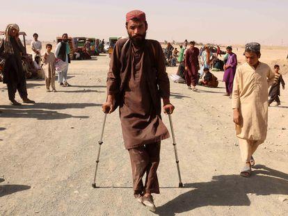 Un grupo de afganos espera para cruzar la frontera de Afganistán con Pakistán.