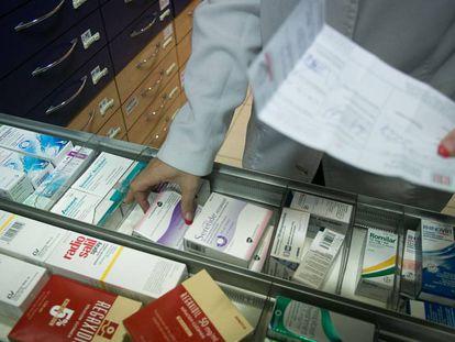 Una farmacéutica revisa unos medicamentos.
