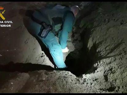 Un agente inspecciona uno de los zulos bajo invernaderos donde la red desmantelada escondía fardos de hachís.