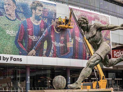 Operarios retiran a Messi de la facha del Camp Nou.