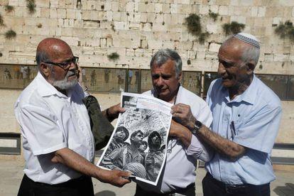 Tres veteranos israelíes de la Guerra de los Seis Días posan en el Muro de las Lamentaciones de Jerusalén con su foto de 1967 en el mismo lugar.