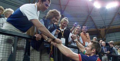Iñaki Urdangarin, capitan de la selección de balonmano, saluda al Príncipe Felipe, a la Reina y a doña Cristina, que lleva en brazos a su hijo Juan Valentín, en los Juegos de Sidney.