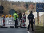 A policeman talks to Germans who are trying to extend their dog walk to the Czech republic on Broumov - Mahring closed Czech -German Border on March 14, 2020. - From March 16, 2020 foreign travel will be banned and foreigners will be barred from arriving in the country. Food stores, pharmacies, banks, post offices, gas stations and takeaway food establishments will be exempt from the closures. (Photo by Michal Cizek / AFP)
