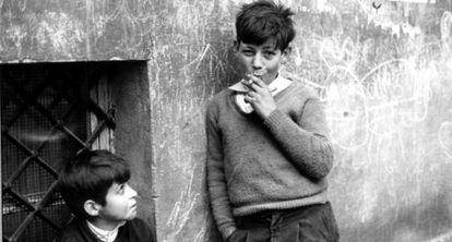 Un niño observa a otro que exhibe una actitud de suficiencia con el cigarrillo.