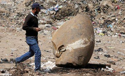 Un hombre pasa junto a la cabeza de la estatua hallada este jueves en una excavación en El Cairo.