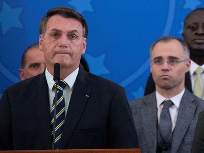 André Mendonça, tras el presidente Bolsonaro, en un acto público en abril de 2020 en Brasilia.
