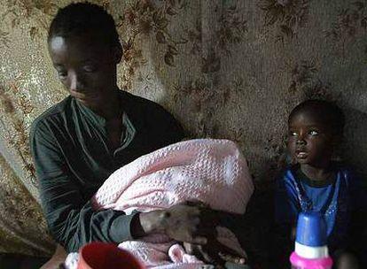 Beatrice Akinyi, de 29 años, seropositiva, con su hijo Ibrahim, de tres años, y su bebé, en su casa de Kibera (Kenia). Contrajo la enfermedad hace cinco años.