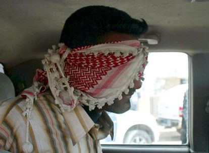 Un detenido en un coche de policía después de haber sido arrestado en Nayaf ayer, durante el combate con el Ejército de Estados Unidos e Iraq.