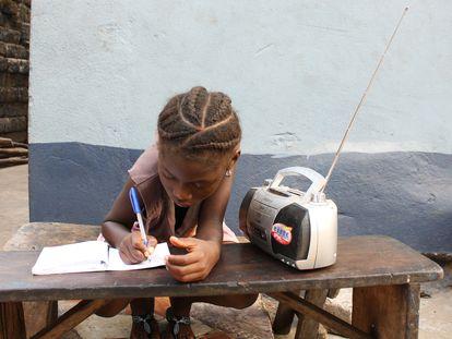Angela Kamara, de seis años, estudia con ayuda de las clases que está escuchando por radio.