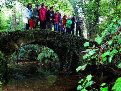 Excursionistas en un puente sobre el río Sarela, en Pontevedra.