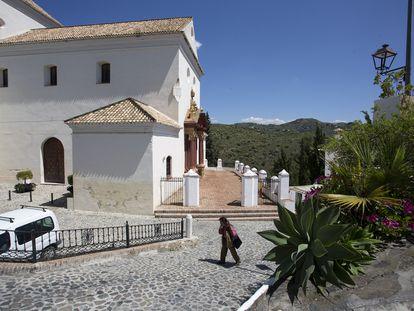 Un vecino pasea junto a la iglesia de Macharaviaya, en Málaga, pueblo sin casos positivos de coronavirus.