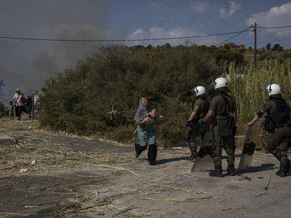 Una mujer refugiada huye con su bebé de las llamas cerca de Mitilene, capital de Lesbos.