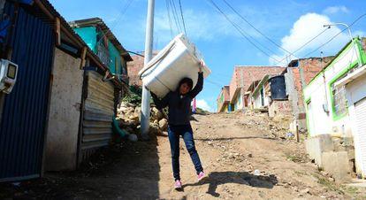 Jessica Hernández carga con una lavadora para alquilarla en Soacha, un barrio marginal de Bogotá (Colombia).
