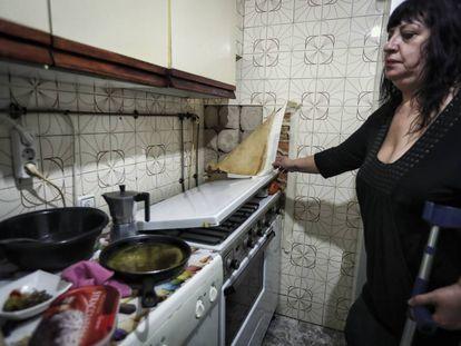 Luisa García muestra el deterioro de la pared de la cocina de su casa en la Colonia Experimental de Villaverde.