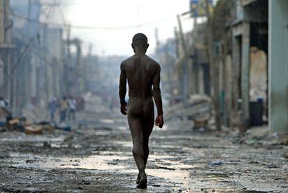 Un hombre camina desnudo y desorientado por una calle arrasada de Puerto Príncipe.