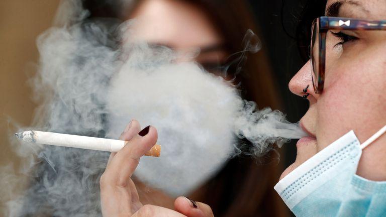 Una mujer fuma con la mascarilla bajada durante la pandemia.