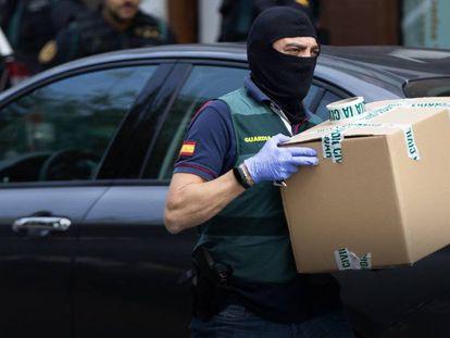 Un agente de la Guardia Civil se lleva material de uno de los domicilios registrados el lunes durante la Operación Judas. En vídeo, los detenidos prestarán declaración en la Audiencia Nacional.