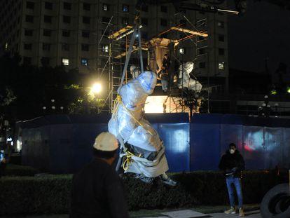 Trabajadores municipales retiran una estatua de Cristóbal Colón en Ciudad de México, en octubre.