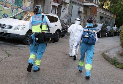 El técnico Andrés, a la izquierda, la médica Marta Calvo (traje blanco) y la enfermera Vanesa Jiménez, en una calle de Madrid, camino de un aviso.