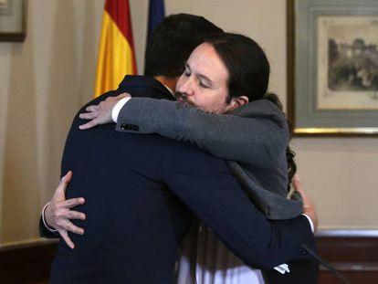 Pedro Sánchez (a la derecha) y Pablo Iglesias se abrazan tras firmar el acuerdo para formar el Ejecutivo en 2019.