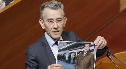El socialista Antonio Torres muestra una foto de Rajoy durante el pleno de este jueves en las Cortes.