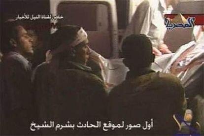 Varias personas suben un cadaver a una ambulancia en una imagen de video tomada de la cadena egipcia El Masriya.