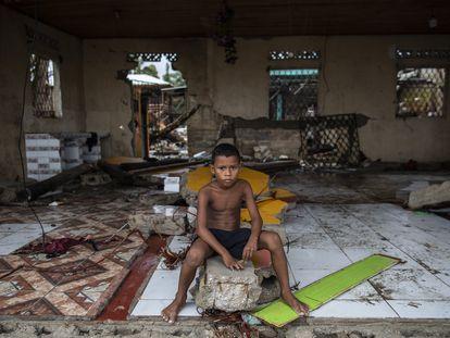 Un niño sentado sobre los escombros de su casa destruida por el huracán Iota en Nicaragua, en Bilwi, el 16 de noviembre de 2020.