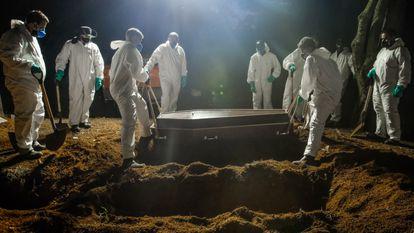 Trabajadores del cementerio de Vila Formosa (São Paulo) entierran un ataud de un fallecido por covid-19.