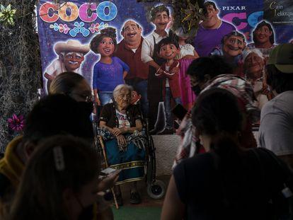 Turistas esperan para hacerse una foto con Salud Ramírez, en Santa Fe de la Laguna, el 15 de marzo.