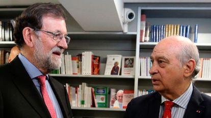 El expresidente del Gobierno Mariano Rajoy conversa con el exministro del Interior Jorge Fernández Díaz en un acto en 2019.
