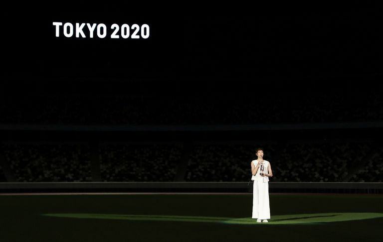 Japanese swimmer Mikado IEEE, with the Olympic torch at the Tokyo Stadium.