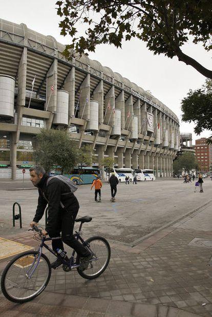 Un ciclista circula frente al Bernabéu, donde se levantará la nueva zona comercial.