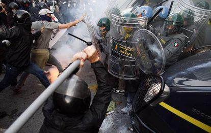 Un grupo de manifestantes se enfrenta con los policías antidisturvios italianos