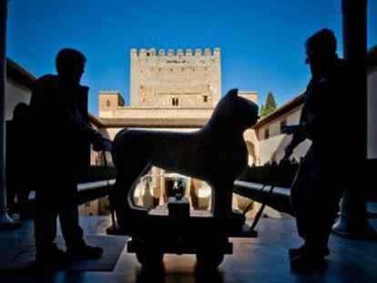 Dos operarios trasladan por el patio de Comares, al fondo la torre, uno de los leones restaurados en 2007.