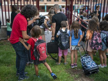 Varios padres se despiden de sus hijos a la entrada del colegio en el primer día de clase en Madrid.